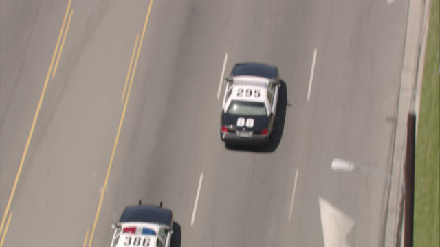 AERIAL OF WHITE SUV DRIVING DOWN STREET AS POLICE CARS FOLLOW FROM BEHIND. COULD BE FOR POLICE ACTION. SURVEILLANCE OR SECURITY.