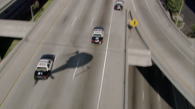 "aerial of police cars with flashing lights or bizbars driving after swerving white suv on highway or 105 freeway. exits for ""highway 405, santa monica, long beach"" visible. man in suv passenger seat shoots gun. gunfire. helicopter shadow visible. speeding - shooting a weapon stock videos & royalty-free footage"
