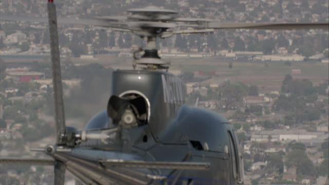 "aerial of black ""lapd n267tv"" police helicopter flying. pass over one story buildings with airplanes. cars driving on highway, cityscape, residential areas or neighborhoods in background. zoom in on helicopter blades and rotors. could be for police action - helicopter stock videos & royalty-free footage"