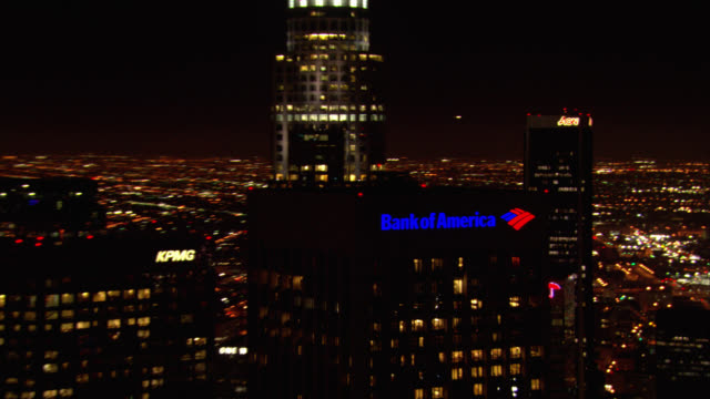 "aerial of downtown los angeles skyline. lighted signs for ""wells fargo"", ""aon"", ""bank of america"". skyscrapers. high rise office buildings. city lights in background. traffic on 110 freeway. - anno 2008 video stock e b–roll"