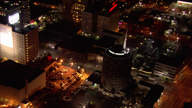 aerial low-speed flying pov over hollywood, sunset strip, sunset boulevard, grauman's chinese theatre movie theater, and capitol records building. zoom in and out on billboards. city skylines. - mann theaters stock videos & royalty-free footage