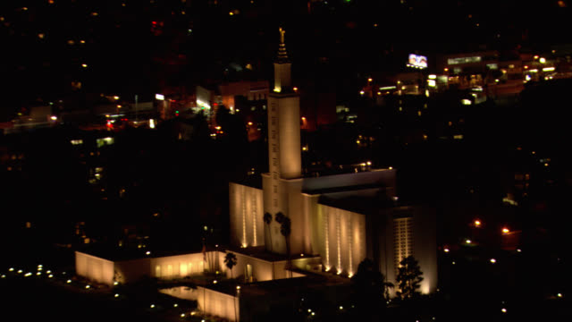 aerial of lights illuminating los angeles mormon temple (lds). religious stone building with palm trees and city skyline. - mormon temple stock videos and b-roll footage