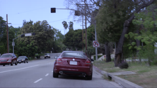 wide angle driving pov straight forward following a mercedes slk 350 car or sedan driving on city streets, sunset blvd near brentwood. upper class neighborhood or suburbs. license plate letitgo1. - brentwood los angeles stock videos & royalty-free footage