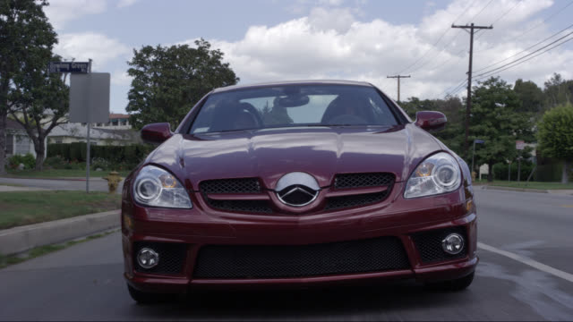 wide angle driving pov straight back of mercedes slk 350 car or sedan driving on city streets, sunset blvd near brentwood. upper class neighborhood or suburbs. - mercedes benz stock videos & royalty-free footage