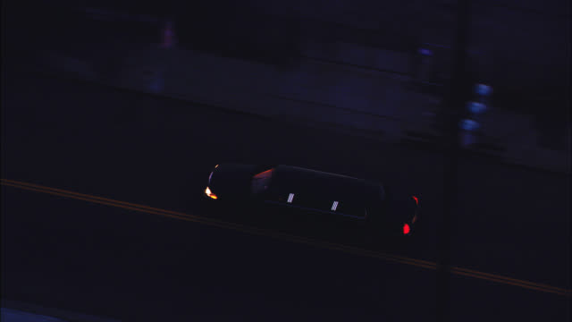 aerial of limo driving around city streets and on freeway or highway. other cars visible. - limousine stock videos & royalty-free footage