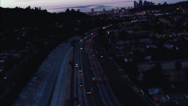 aerial of cars driving on freeway or highway leading out of san fernando valley into downtown los angeles. los angeles skyline visible. high rises and skyscrapers. us bank tower visible. sunset. could be 5 freeway. - us bank tower stock videos & royalty-free footage