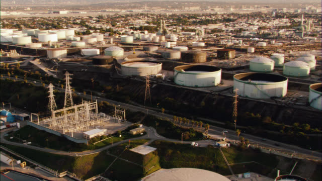 aerial of oil refinery or power plant on coast. beach and sand visible. beachfront city. could be manhattan beach. freeway or highway visible. camera zooms in on limo. - power station stock videos and b-roll footage