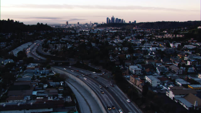 aerial of cars driving on freeway or highway leading out of san fernando valley into downtown los angeles. camera focuses on limo. los angeles skyline visible. high rises and skyscrapers. us bank tower visible. sunset. could be 5 freeway. - us bank tower stock videos & royalty-free footage