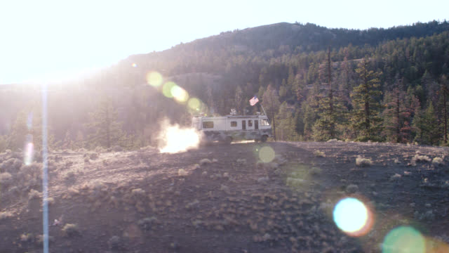 aerial of rv driving on dirt road or hill surrounded by trees. could be forest. could be campgrounds or national park. mountains in bg. - camper van stock videos and b-roll footage