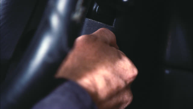 close angle of man's hand putting key into ignition. series. - 車のキー点の映像素材/bロール