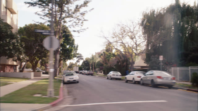 process plate 3/4 right back of apartment building in urban residential area. could be miracle mile or fairfax area. pedestrians. cars parked on curb. - los angeles county stock-videos und b-roll-filmmaterial