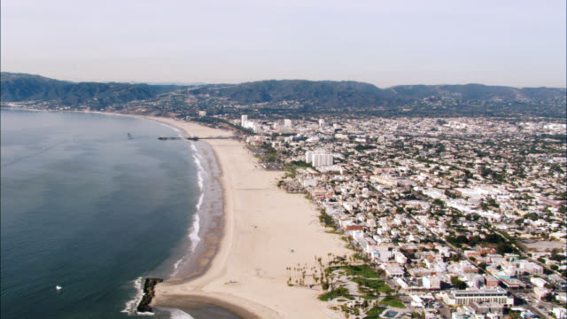 vídeos de stock e filmes b-roll de aerial of coastline or coast. manhattan beach and santa monica piers visible. condominiums and beach houses. beach or shore. mountains visible in bg. - santa monica