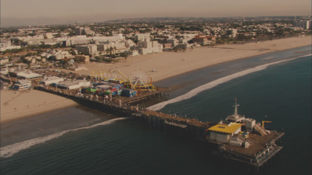 AERIAL OVER SANTA MONICA PIER. ROLLER COASTER AND FERRIS WHEEL VISIBLE. COASTLINE AND BEACH. BUILDINGS, CONDOMINIUMS, AND BEACH HOUSES VISIBLE. MOUNTAINS IN BG.