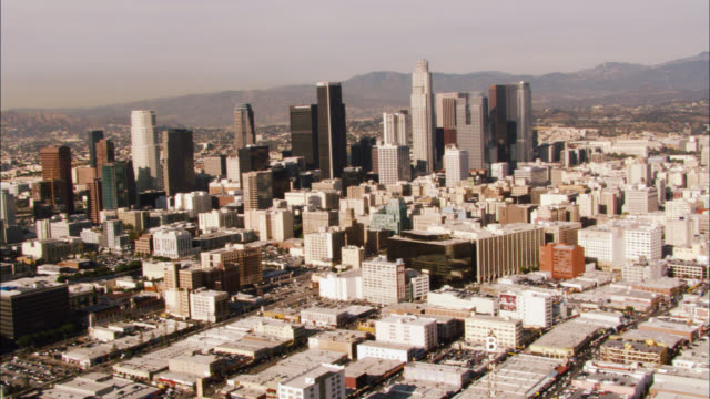 aerial over downtown los angeles skyline. cities. us bank tower visible. high rises and skyscrapers. mountains in bg. - us bank tower stock videos & royalty-free footage