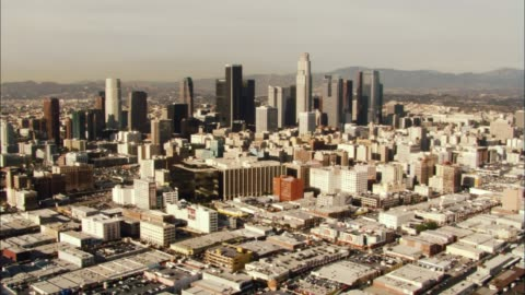 aerial zoom in over downtown los angeles skyline. cities. us bank tower visible. high rises and skyscrapers. mountains in bg. - us bank tower bildbanksvideor och videomaterial från bakom kulisserna