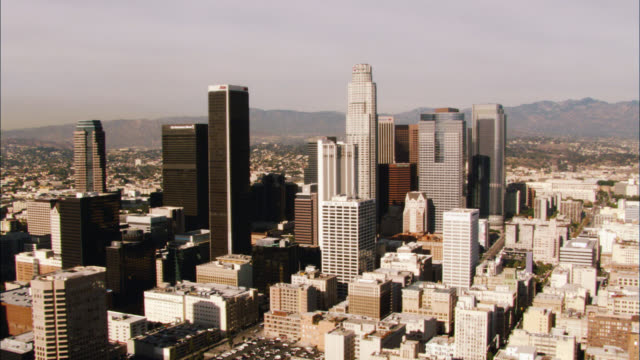 aerial zoom in over downtown los angeles skyline. cities. us bank tower visible. high rises and skyscrapers. mountains in bg. freeway visible. - us bank tower stock videos & royalty-free footage