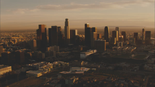 aerial of downtown los angeles city skyline at sunset. high rises and skyscrapers. mountains in bg. us bank tower. office buildings. - us bank tower stock videos & royalty-free footage