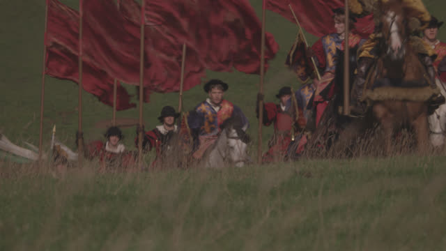 wide angle of renaissance guards, entourage, military escort or royal procession on horseback riding through countryside. flags or banners waving could be nobility. upper class. - renaissance stock-videos und b-roll-filmmaterial