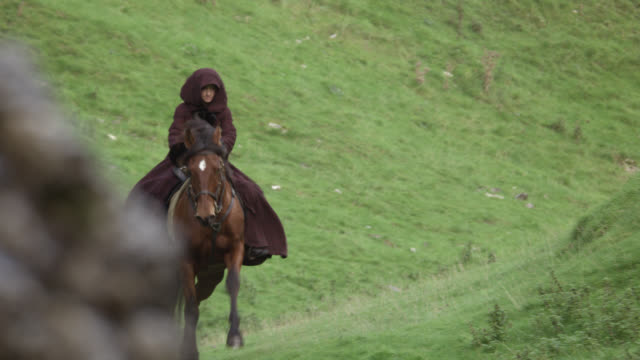 pan left to right of woman on horseback riding through valley. grass-covered hills or mountains. countryside. - hooved animal stock videos and b-roll footage