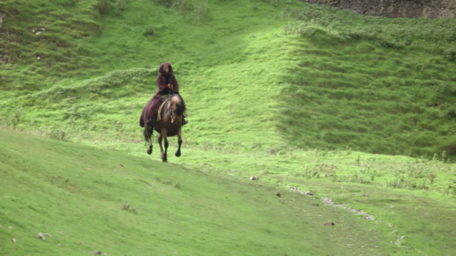 PULL BACK OF WOMAN RIDING ON HORSEBACK THROUGH VALLEY BETWEEN GRASS-COVERED MOUNTAINS OR HILLS ON PATH OR TRAIL. COUNTRYSIDE.