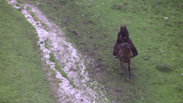 tracking shot of woman riding on horseback through valley between grass-covered mountains or hills on path or trail. countryside. rocky cliffs. - hooved animal stock videos and b-roll footage