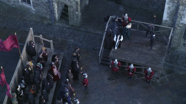high angle down of woman, prisoner being led to platform for execution or death penalty in courtyard. crowd of people, spectators or townsfolk and guards. upper class, nobility or gentry. renaissance. stone buildings in bg. could be tower of london. actua - hinrichtung stock-videos und b-roll-filmmaterial