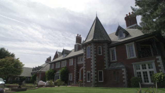 pan down to two story, upper class brick house, mansion or estate. could be a manor.  los angeles area. lawns. turret and dormer windows. - zweistöckiges wohnhaus stock-videos und b-roll-filmmaterial