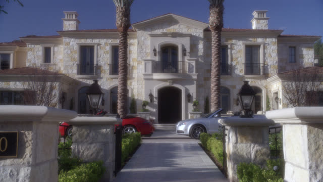 stockvideo's en b-roll-footage met pan down to two story, upper class, stone mansion or house. convertible cars parked in front. landscaped yard and lawn. los angeles area. - landhuis