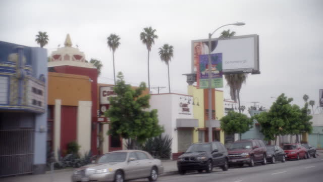 wide angle driving pov of city streets in lower to middle class urban area. commercial area, storefronts, shops and restaurants. church. pico blvd. cars. mid-city. overcast. - middle class stock videos and b-roll footage