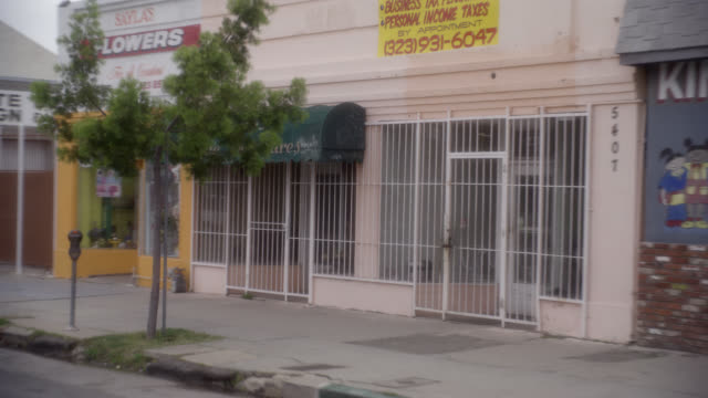 wide angle driving pov of city streets in lower to middle class urban area. commercial area, storefronts, shops and restaurants. pico blvd. cars. mid-city. overcast. - middle class stock videos and b-roll footage