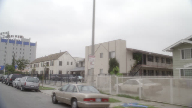 wide angle driving pov of city streets in lower to middle class urban area. commercial area, storefronts, shops and restaurants. two-story middle class houses in residential area or neighborhood. crenshaw and pico blvd. cars. mid-city. overcast. - middle class stock videos & royalty-free footage