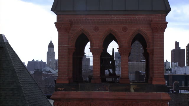 medium angle of bell tower, steeple, or spire of church or temple. skyline visible in bg. blue sky and clouds. roofs and rooftops. - steeple stock videos & royalty-free footage