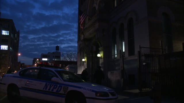 vídeos de stock e filmes b-roll de medium angle of nypd police car and van parke outside building with american flag over entrance. could be police station, precinct, or headquarter. police officers and detectives enter and exit building. - detetive