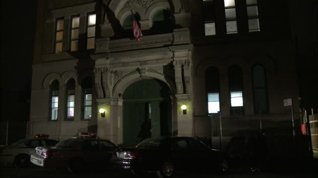WIDE ANGLE OF POLICE STATION, PRECINCT, OR HEADQUARTERS. AMERICAN FLAG ABOVE ENTRANCE. POLICE CARS PARKED OUT FRONT. POLICE OFFICERS AND DETECTIVES ARE VISIBLE ENTERING AND EXITING BUILDING.