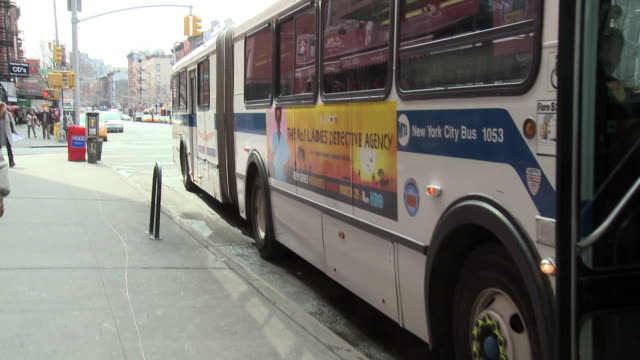 medium angle of city bus parked on curb of urban area street. bus pulls away once passengers get on. city street. pedestrians. - 商業車点の映像素材/bロール