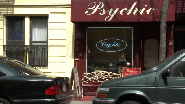 """vídeos de stock, filmes e b-roll de medium angle of storefront window with awning for """"psychic."""" urban area. cars parked on curb. bench and signs in front of shop. - 2009"""