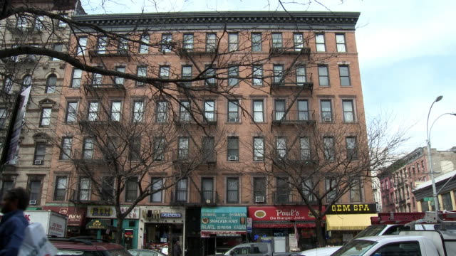 stockvideo's en b-roll-footage met up angle of multi story brick apartment building in urban area. pedestrians walk by in fg. bare tree branches. - bare tree