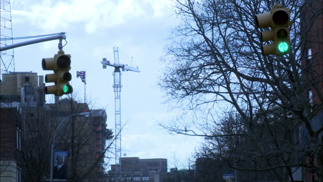 stockvideo's en b-roll-footage met medium angle urban area. stoplights over street and crane in bg. bare tree branches. - bare tree