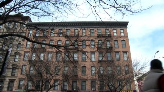 vídeos y material grabado en eventos de stock de up angle of multi story brick apartment building in urban area. pedestrians walk by in fg. bare tree branches. - salida de incendios