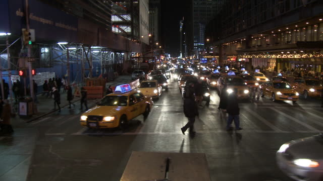 wide angle driving pov through times square of crowds of people or pedestrians on sidewalk. commercial area, shops and stores. neon lights and signs. cars and taxis on city streets. port authority bus terminal or station. - port authority stock videos & royalty-free footage