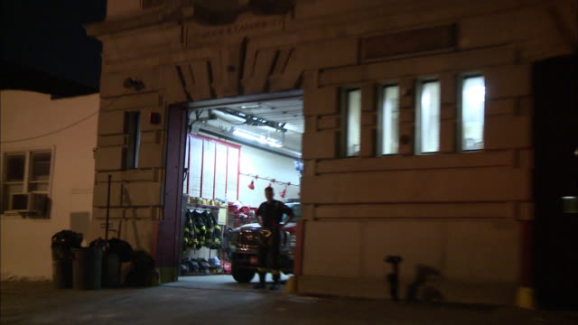 wide angle driving pov straight back of a police car with bizbar, flashing light, cars driving on city street past three story brick buildings, cars parked on both sides of one way street. headlights. pass fire engine company 258 fire station with firefig - fire station stock videos & royalty-free footage
