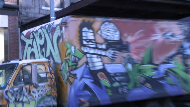 zoom in on graffiti art on side of truck parked along 14th street, near 9th ave. urban area. west village, manhattan. - グラフィティ点の映像素材/bロール