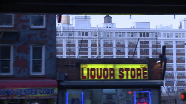 wide angle driving pov of stores, shops and multi-story brick apartment buildings along city street. liquor store. park avenue under brooklyn-queens expressway. - liquor store stock videos and b-roll footage