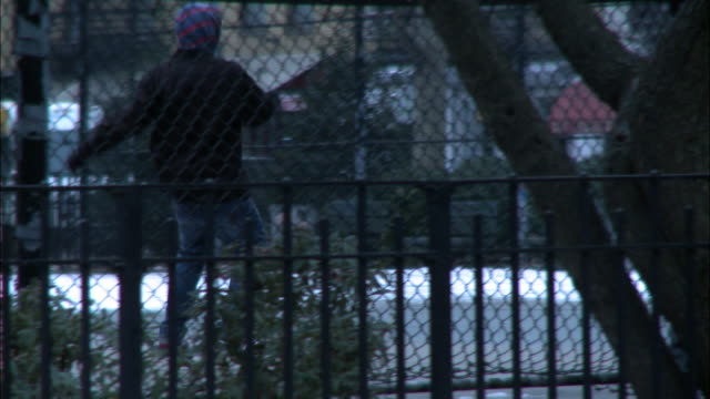 medium angle of young man or teenager skateboarding in park behind chain link fence. could be east village or lower east side of manhattan. - lower east side bildbanksvideor och videomaterial från bakom kulisserna