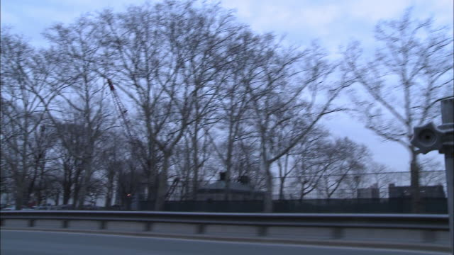 wide angle driving pov of cars on city streets, fdr dr. middle class high rise and multi-story brick apartment buildings. east river park. williamsburg bridge. construction cranes in bg. urban area, lower east side of manhattan. - williamsburg bridge stock videos and b-roll footage
