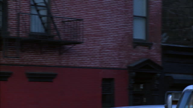 "stockvideo's en b-roll-footage met hand held driving pov from right side of car on new york city street in commercial area. pass tree lined streets with high rise and skyscraper office buildings in bg, ""westside famous deli,"" cars parked on street, trees with bare branches, pedestrians, pe - bare tree"