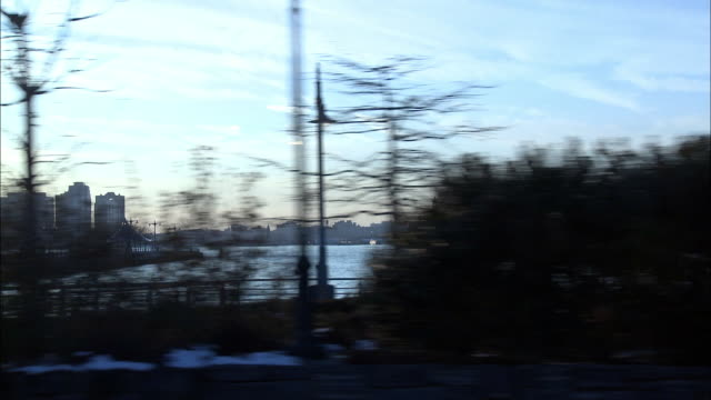 WIDE ANGLE DRIVING POV FROM RIGHT SIDE OF CAR DRIVING ON NEW YORK CITY STREET ALONG HUDSON RIVER. HOBOKEN TERMINAL CLOCK TOWER AND HIGH RISE OFFICE BUILDINGS ON NEW JERSEY SHORELINE IN BG. PEOPLE RIDING BICYCLES ON BIKE PATH IN FG. TREES WITH BARE BRANCHE