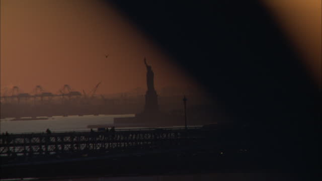 vidéos et rushes de wide angle driving pov from right side of car driving on manhattan bridge over east river. pass brooklyn bridge with statue of liberty in bg. landmarks. - port de new york