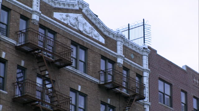 vídeos y material grabado en eventos de stock de pull back from multi-story brick building, apartment building, with fire escapes on side of building to people walking on sidewalk of city street. patches of snow on the ground. brooklyn. - salida de incendios