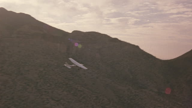 a-a aerial tracking shot l-r of small propeller airplane flying over desert landscape. plane flies over desert canyons and mountains with sparse vegetation. air-to-air. - propeller video stock e b–roll